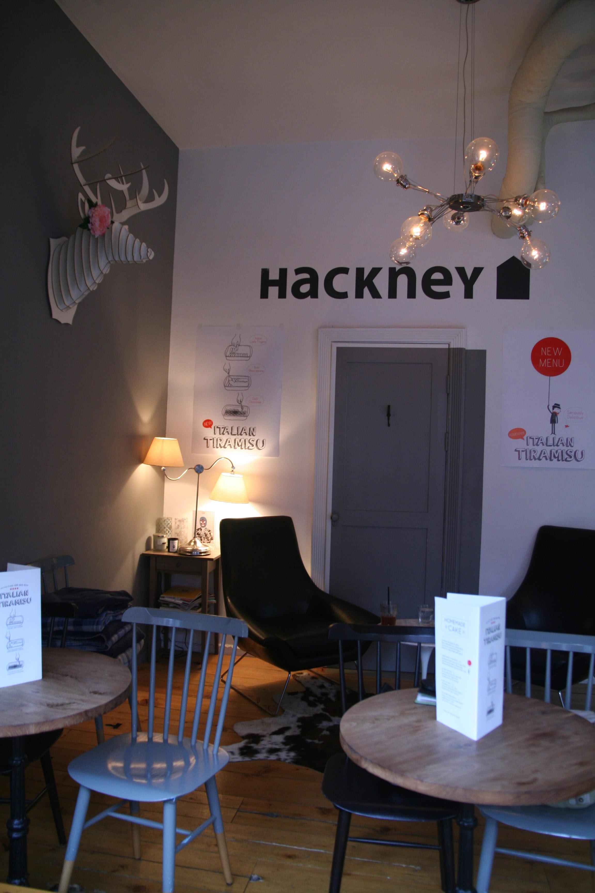 해크니의 내부 모습. 흰 벽에 검은 글자로 HACKNEY라고 쓰여 있고, 한쪽 벽면은 회색으로 페인트칠이 되어 있으며 위쪽에 사슴의 머리 모양 모형이 매달려 있다. 아래에는 회색으로 된 화장실 문, 그리고 나무로 되어 있는 동그란 테이블 두 개와 철제 의자들이 놓여 있다.