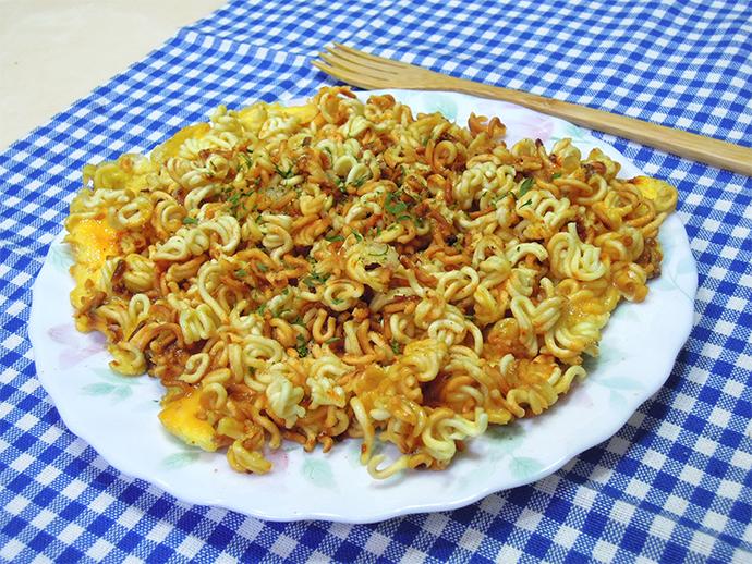 라면과 달걀 그리고 설탕으로 요리한 '라며노미야끼'의 모습이다. 파란색 체크 보자기 위에 흰 접시, 그리고 그 위에 라며노미야끼가 있다. 노릇하게 구워진 라면 부스러기와 달걀, 그리고 라면 수프와 설탕이 위에 뿌려져 있어 주황빛이 돌고 있다.