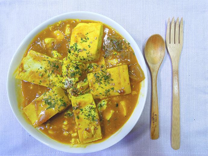 김치 카레 두부의 외양이다. 노란색으로 물든 두부 5개가 벚꽃잎 모양으로 원을 만들며 포개져 있다. 이 접시 오른쪽으로 수저와 포크가 놓여 있다.