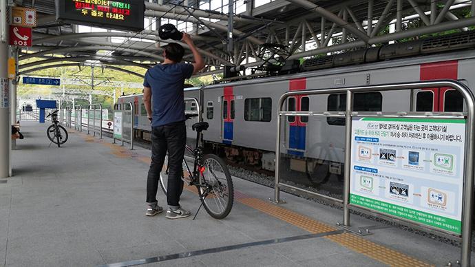 남학생이 손에 자전거를 지탱하고 지하철역에서 지하철을 기다리고 있다. 반대편에 도착한 지하철이 보인다.
