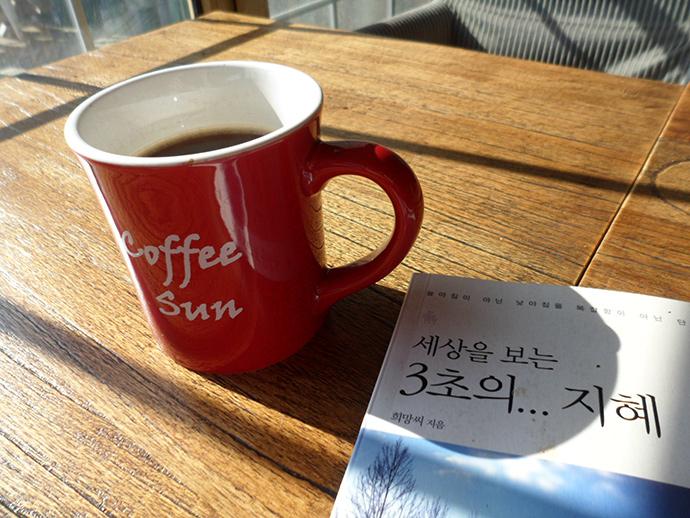 카페 식탁 위에 커피 잔과 책이 놓여져 있는 사진. 옆에 창문에서 햇살이 들어오고 있고 따뜻한 분위기이다. 책에는 '세상을 보는 3초의 지혜'라는 제목이 쓰여있다.