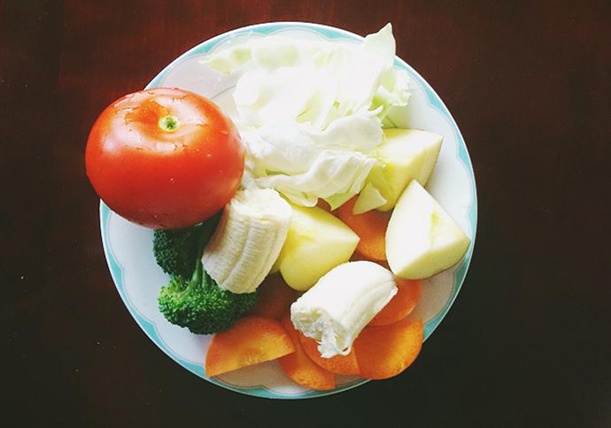 접시 위에 양배추, 사과, 당근, 바나나, 브로콜리가 잘라져 있다. 토마토는 잘리지 않은 온전한 모양이다
