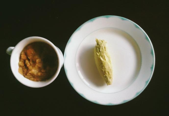 위에서 찍은 사진. 왼쪽 컵에 해독 주스가 담겨 있고, 접시 위에 고구마가 하나 놓여 있다.