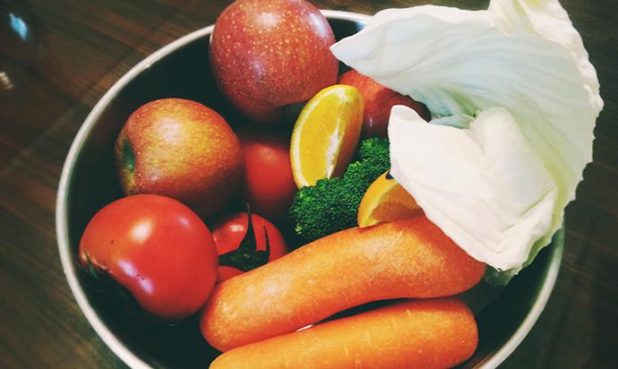 은색 보울 안에 사과, 토마토, 오렌지, 브로콜리, 양배추, 당근이 들어가 있다.
