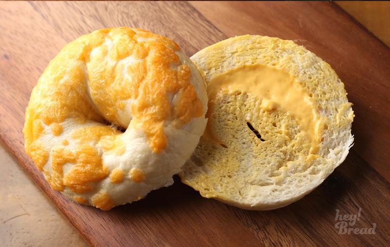 치즈카이거 베이글의 사진. 소보로처럼 생긴 베이글이 반으로 갈라져 있고, 아래쪽 베이글에는 노란색 치즈가 가득 발려져 있다.