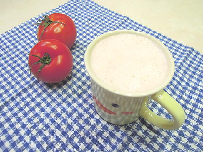 토마토 우유가 노란색 병아리가 그려진 컵에 담겨있다. 컵 왼쪽으로는 빨간 토마토 2알이 놓여있다.