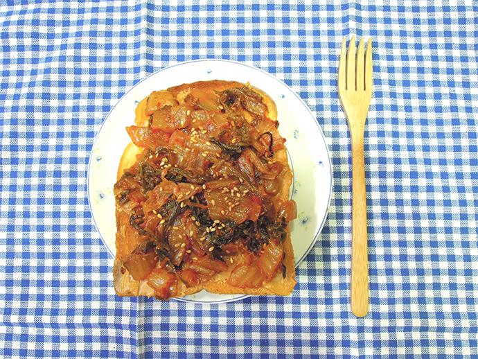 왼쪽은 땅콩 김치 식빵의 정면 사진이다. 볶은 김치와 깨가 올라간 식빵접시가 왼쪽에 있고 오른쪽에 나무로 만든 포크가 있다.