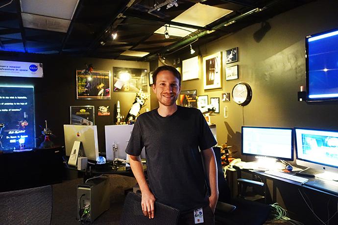어두침침한 스튜디오에 영상디자이너 Brian이 서 있다. 그 뒤로는 우주 관련 피규어들이 보인다.
