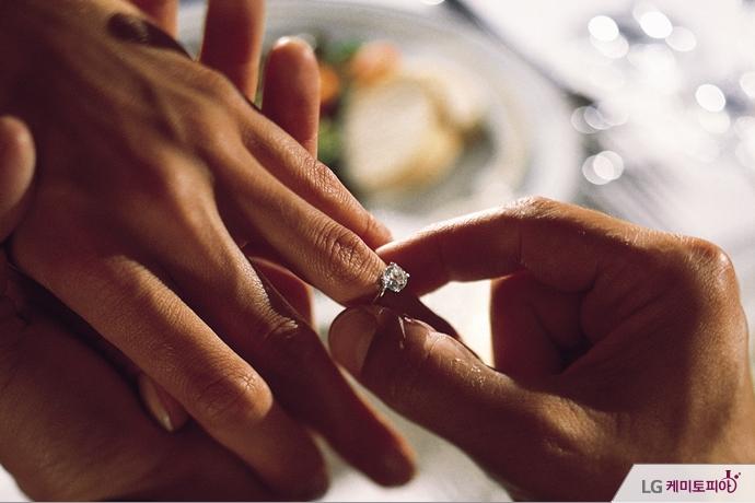 한 남성의 손이 다른 여성의 손가락에 다이아몬드 반지를 끼워주고 있다.