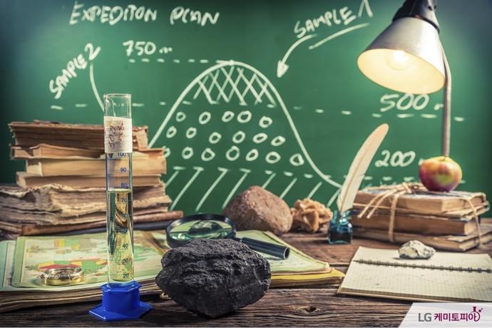 책상 위에 석유와 석탄, 책 등이 놓여있고, 칠판에는 지층에 관한 내용이 적혀있다.