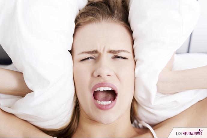 한 여성이 베개로 귀를 막으며 괴로워하고 있다.