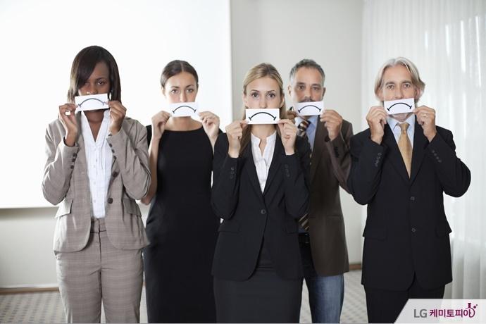 못마땅한 표정을 짓고 있는 회사원 그룹.