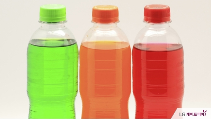 다양한 색깔의 음료들이 투명 플라스틱 병에 담겨 있다.