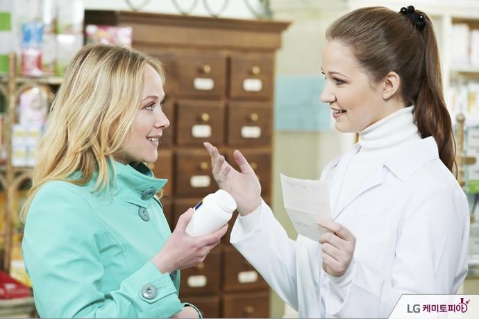 한 고객이 약을 들고 약사와 이야기하고 있다.