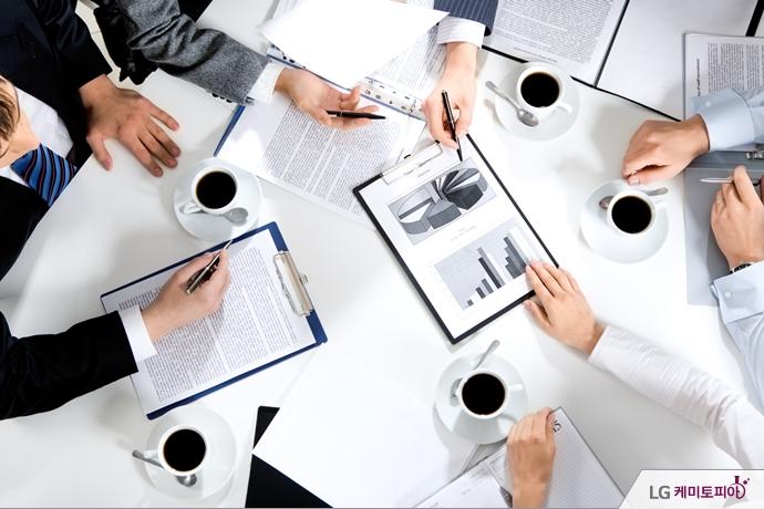 회의 중인 테이블에 여러 서류와 함께 커피가 놓여 있다.