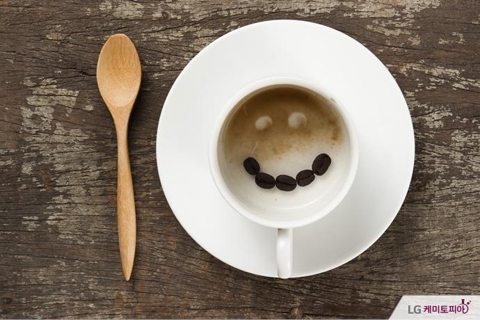 비어있는 커피 잔 속에 커피콩들이 웃는 얼굴을 형상화하고 있다.