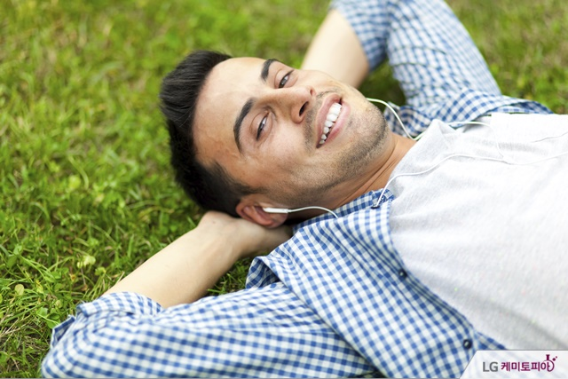 남성이 잔디 위에서 음악을 들으며 미소를 짓고 있다
