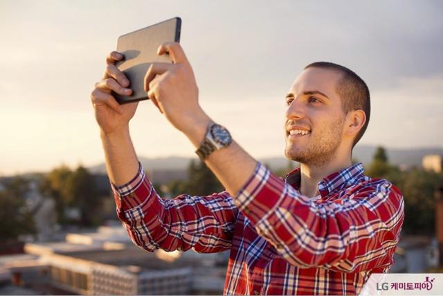남성이 태블릿 PC를 보면서 미소를 짓고 있다.