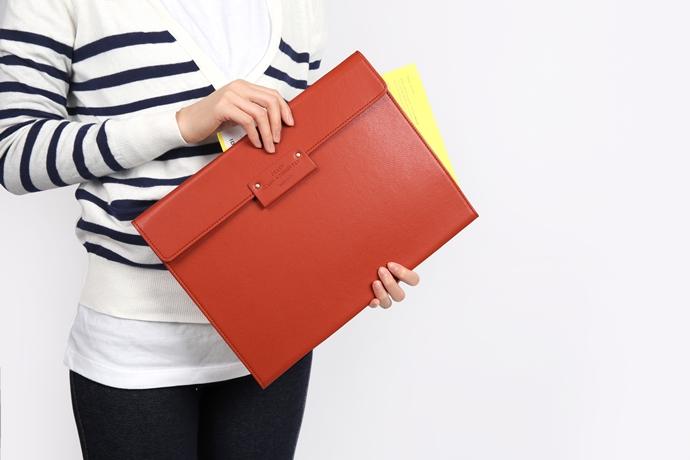 한 여성이 주황색 파일을 들고 있다.