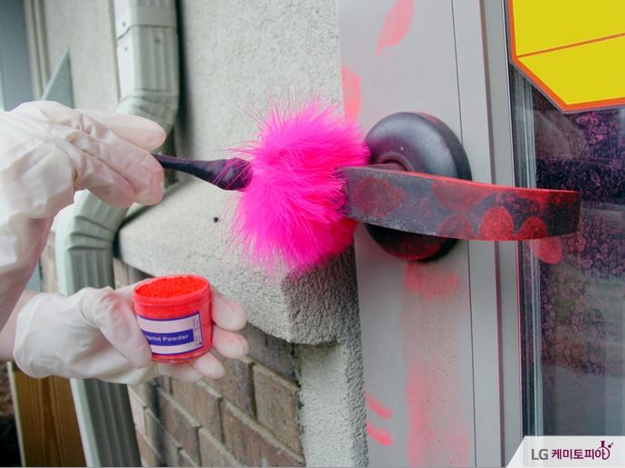 핑크색 가루가 묻은 붓으로 지문을 채취하고 있다.