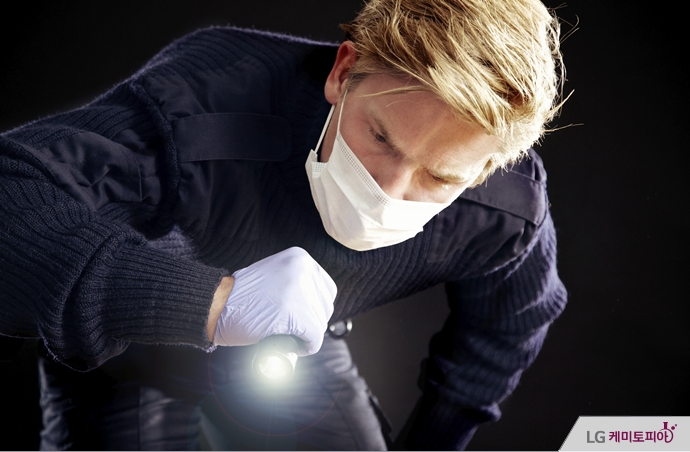 마스크 쓴 남성이 손전등으로 무언가를 살피고 있다.