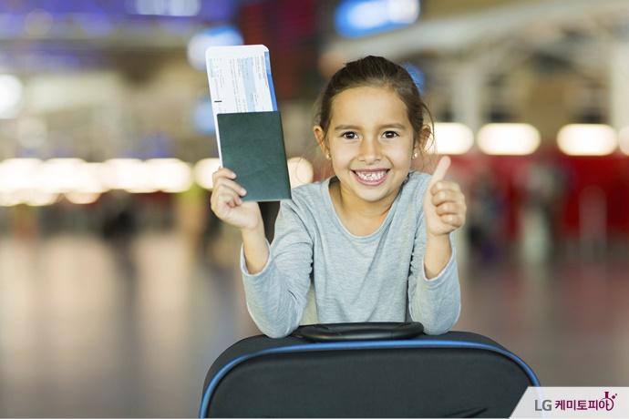 공항에서 항공권을 들고, 엄지손가락을 들고 있는 여자아이