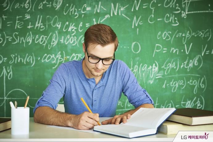 여러 화학식이 써진 칠판 앞에서 책과 노트를 보고 있는 남자