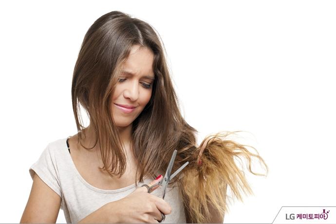 갈라진 머리카락 끝을 가위로 자르려는 여성