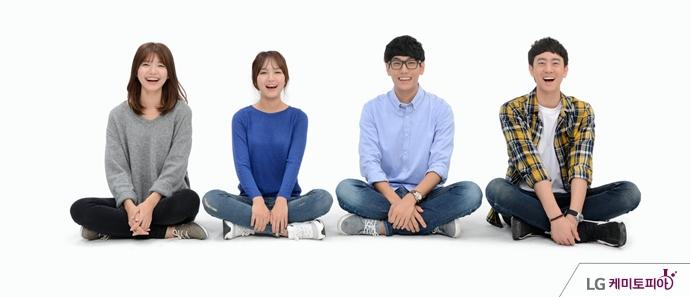 남녀 4명이 웃으며 바닥에 앉아있다.