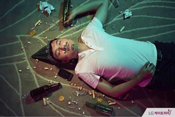 한 남자가 술병을 손에 쥐고 쓰러진 채 잠들어 있다