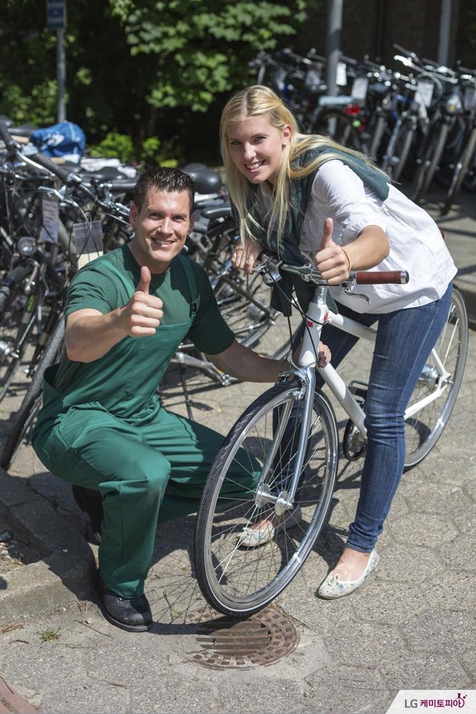 점원과 함께 자전거를 고른 여성이 점원과 함께 엄지를 치켜세웠다.