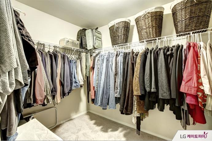 옷걸이에 많은 옷들이 걸려있는 드레스룸