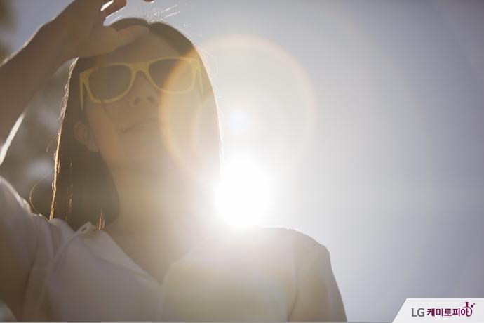 선글라스를 끼고 햇빛을 가리고 있는 여자