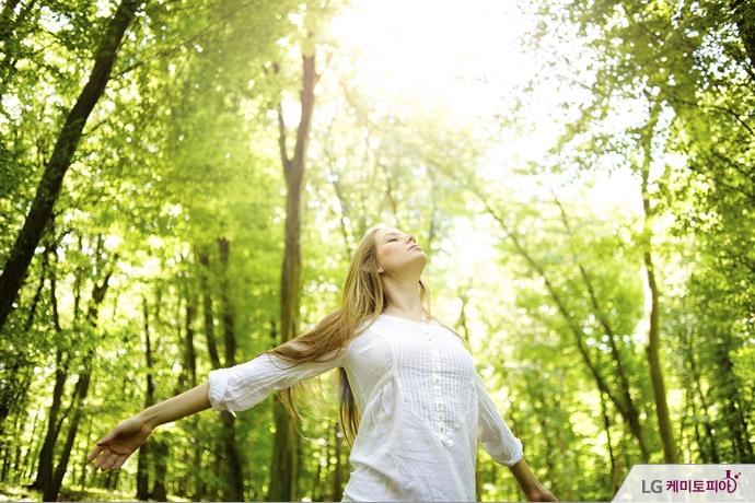 숲 속에서 크게 숨을 들이마시는 여자