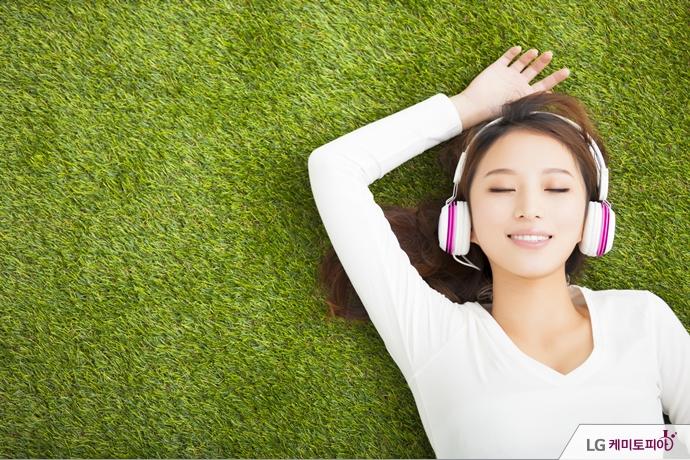 잔디 위에 누워 음악을 듣는 여자