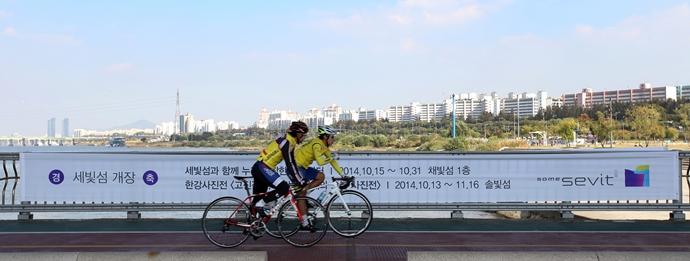한강 다리를 자전거를 타고 달리는 남자들