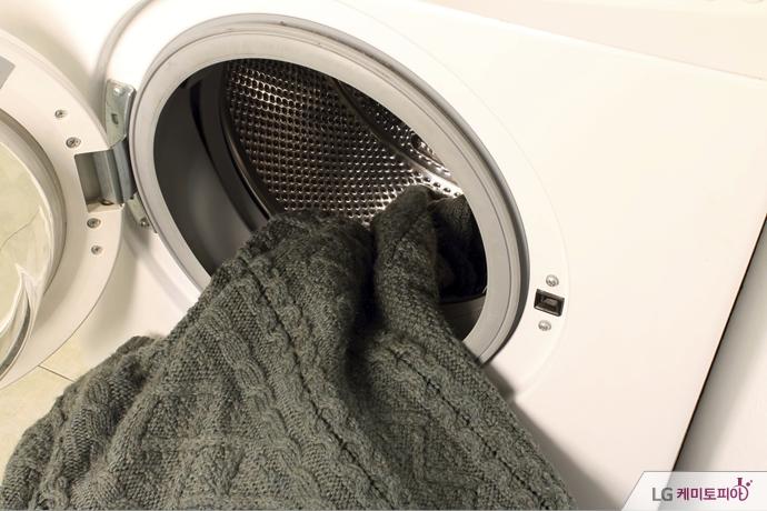 세탁기에서 세탁을 마친 니트 스웨터