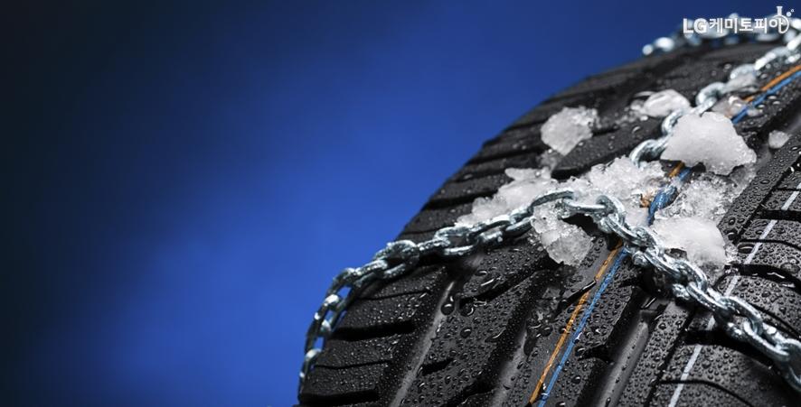 자동차 타이어에 스노우 체인이 씌워져 있다.