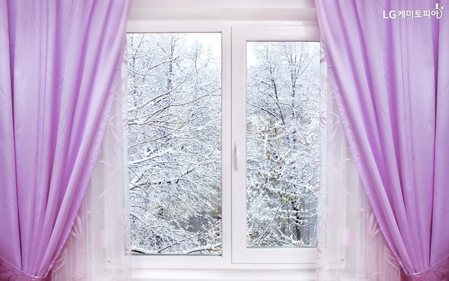 겨울 눈쌓인 바깥이 보이는 창문 안에 도톰한 커튼이 쳐져 있다.