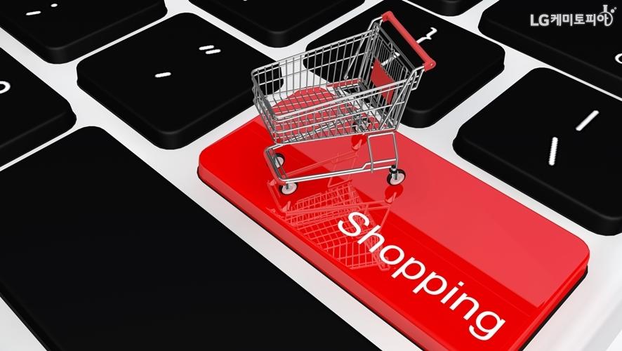 노트북 키보드 '쇼핑'이라고 적인 자판 위에 카트 미니어쳐가 놓여져 있다.