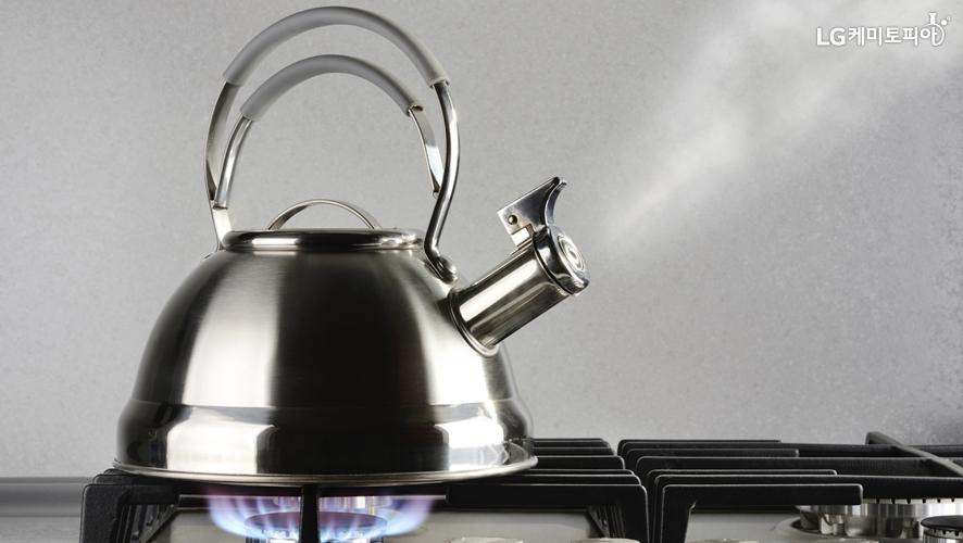 끓고 있는 주전자에서 수증기가 나오고 있다.
