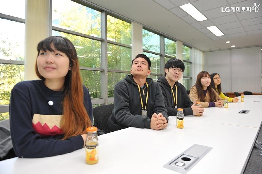테이블에 앉아 설명을 듣고 있는 대학생 에디터들