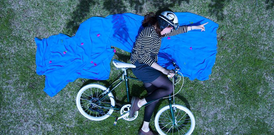 잔디밭에 파란 천을 깔고 자전거를 눕힌 채 올라탄 여자의 사진