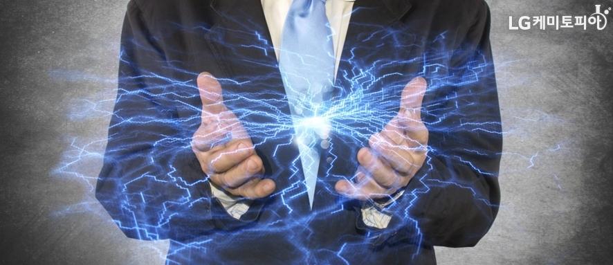활짝 벌린 양 손바닥 사이에 파란색 전류가 흐르는 사진