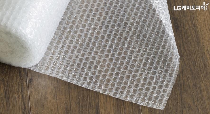 마룻바닥에 펼쳐져 있는 에어캡 두루마리