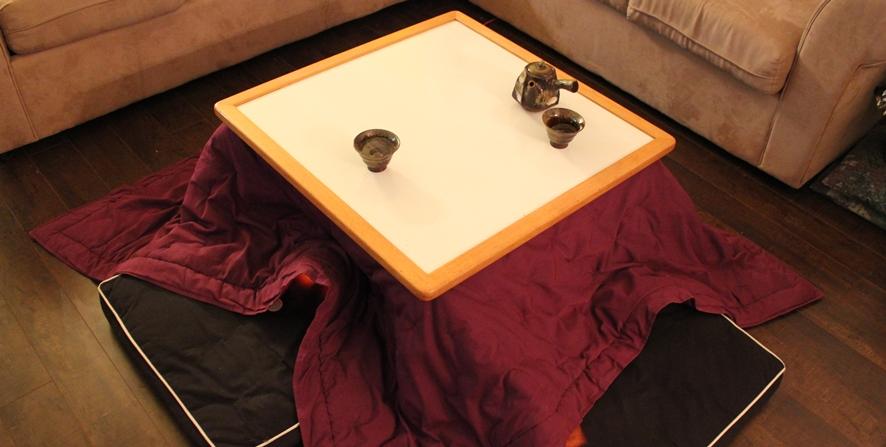 소파가 있는 거실 중앙에 자주색 이불을 씌운 코타츠가 놓여져 있다.