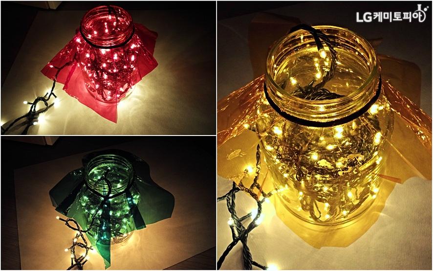 꼬마전구 전원을 켜자 셀로판지 색에 따라 각각 빨강, 노랑, 초록으로 빛나는 유리병 속 전구 사진.