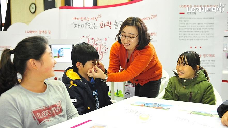 선생님이 직접 만든 화학 놀잇감을 아이와 함께 보고 있다.