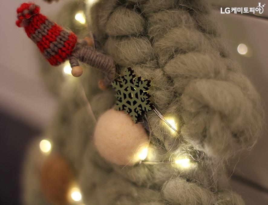 목도리 위에 크리스마스 장식과 조명이 어우러져 있다. 사진 중앙 크리스마스 사진만 또렷하게 초점이 맞고 사진 바깥 쪽은 흐리게 보인다.