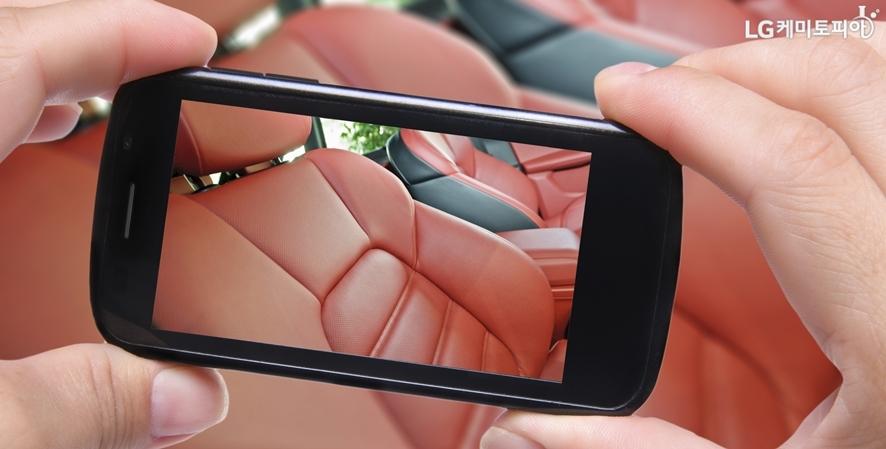 차동차 내부의 붉은 계통 시트를 찍는 스마트폰 화면
